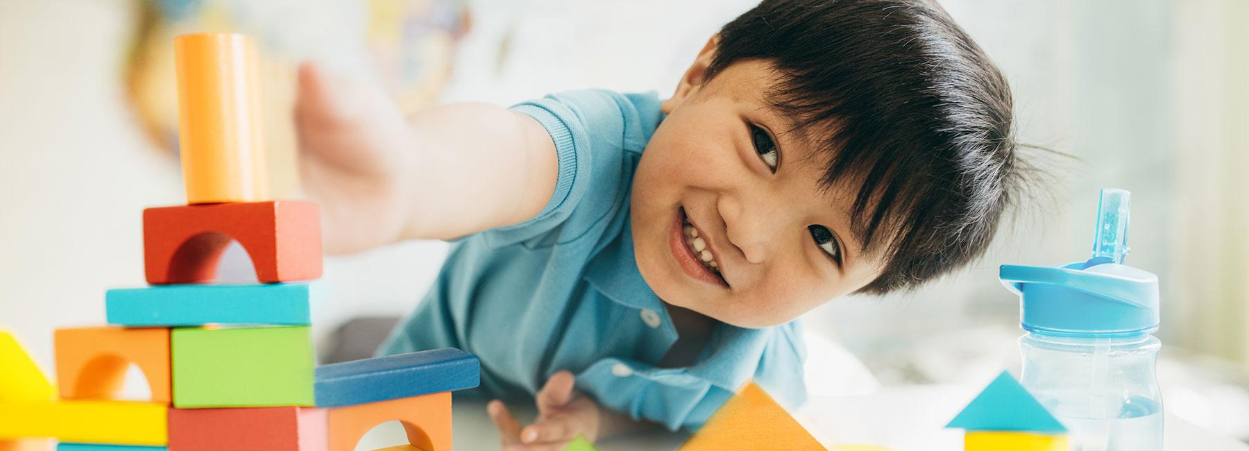 Un garçon construit une tour de blocs